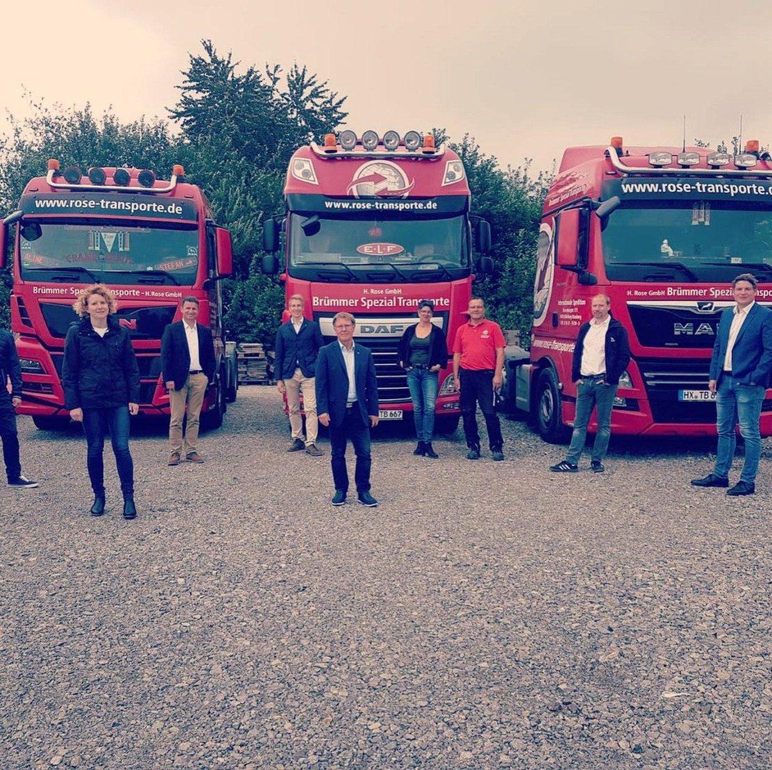 Teilnehmer des Dorfrundgangs vor Speditions-LKWs
